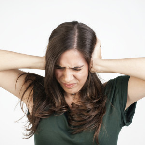 Young woman with her hands covering her ears not to hear noise.